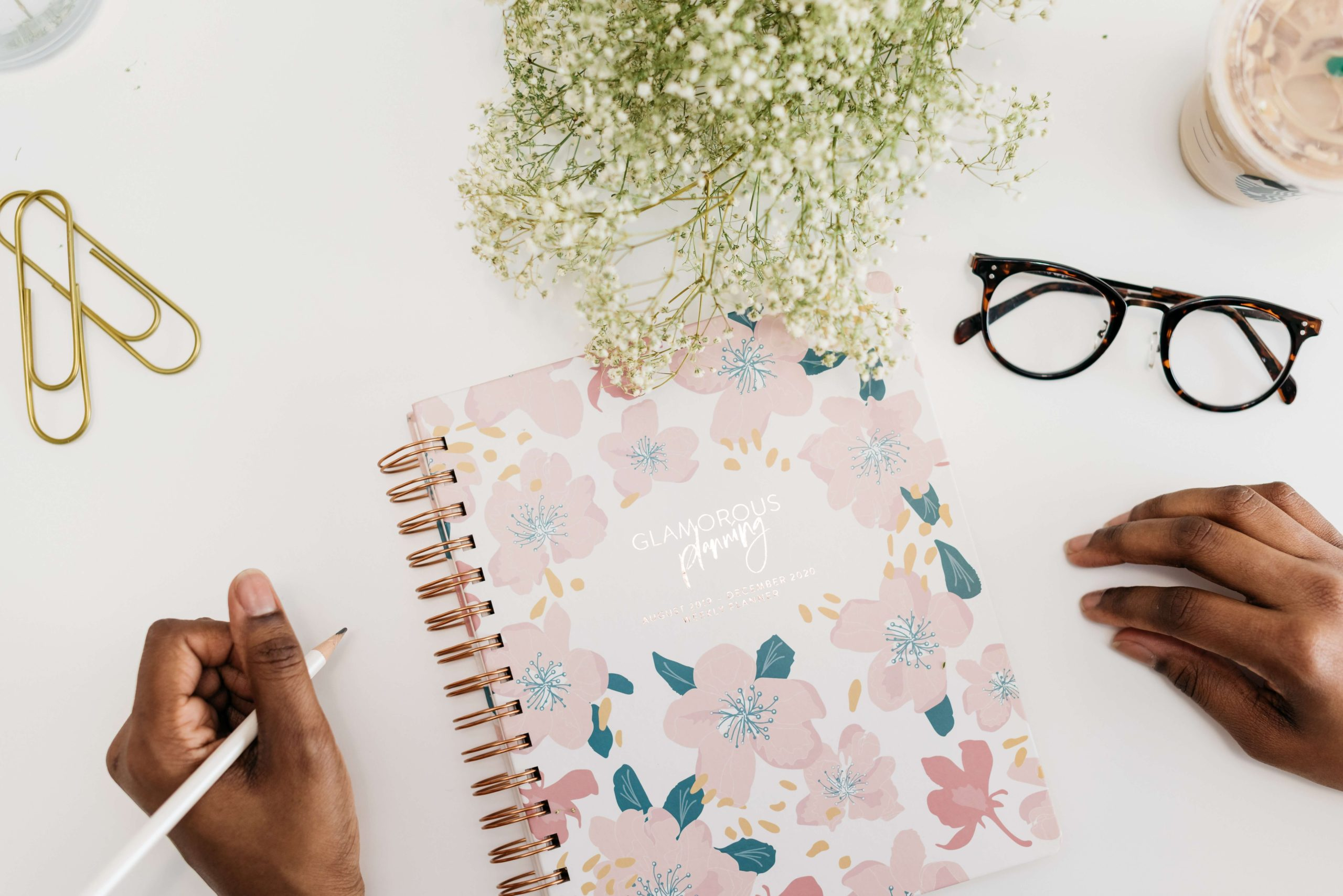 woman holding pen with notebook, flowers, and glasses