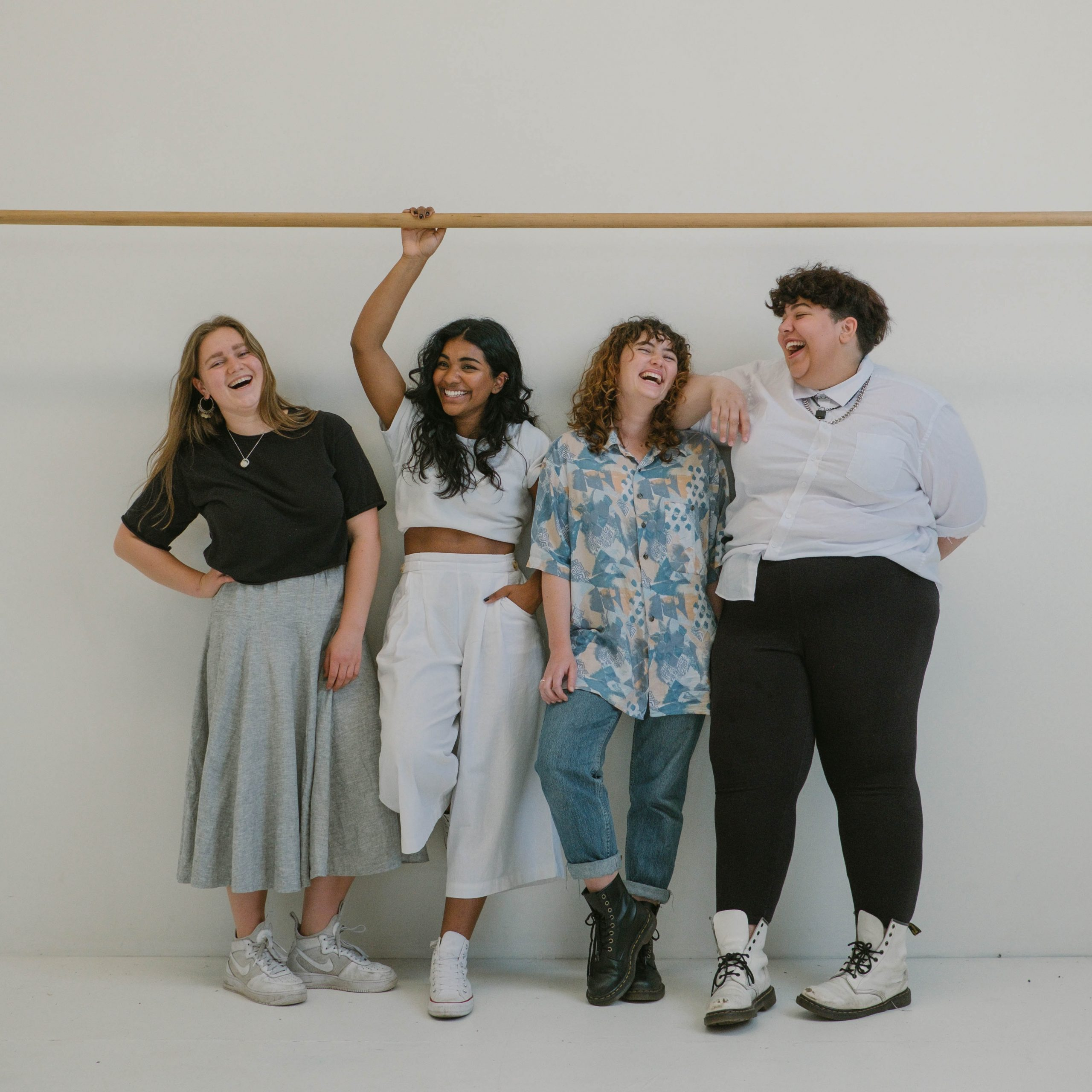 four diverse women smiling with each other