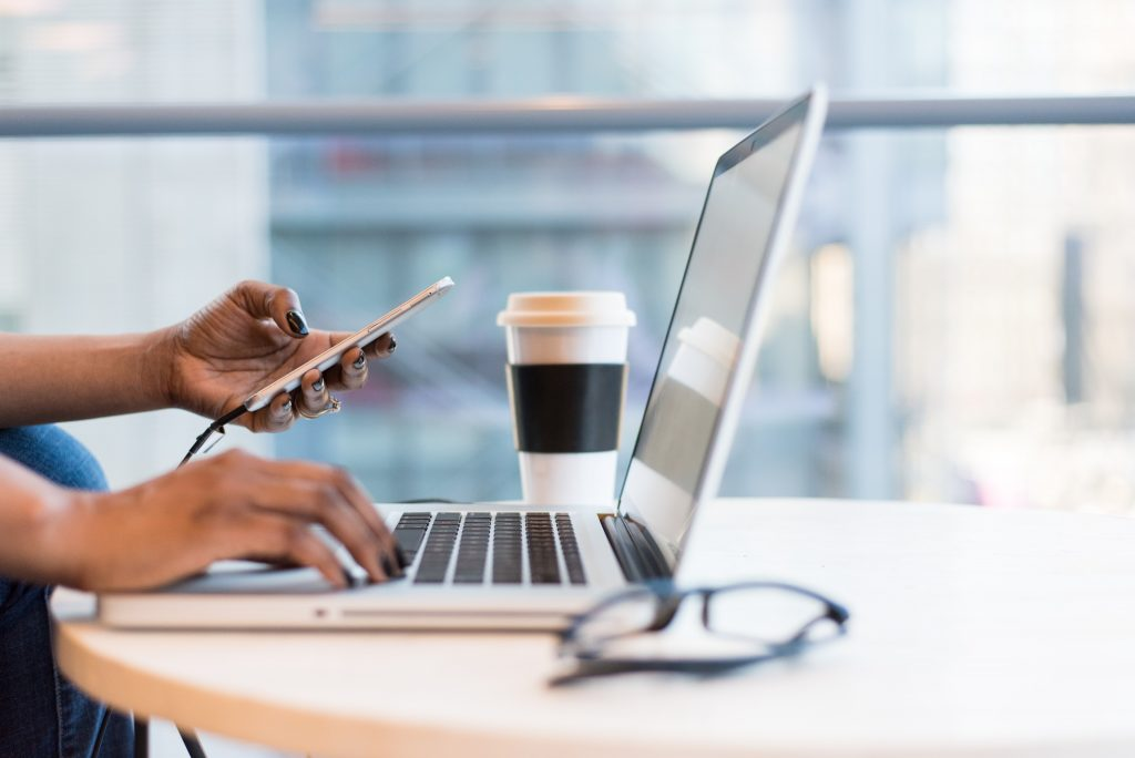 Black business owner holding phone and typing on laptop