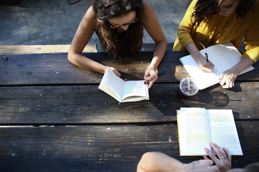 womxn sitting together at an outdoor picnic table reading books and writing notes