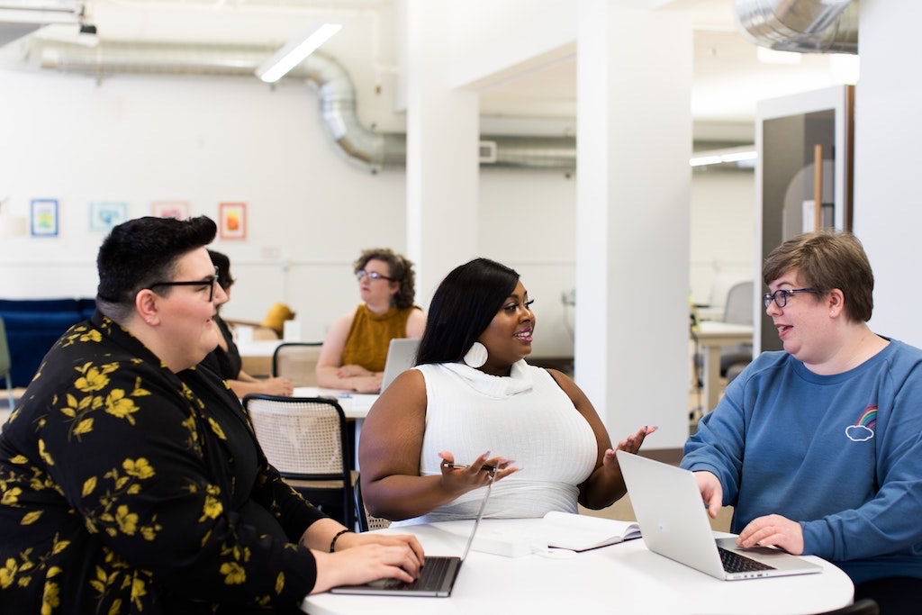 group of three plus-size womxn sitting around a table and discussing happily