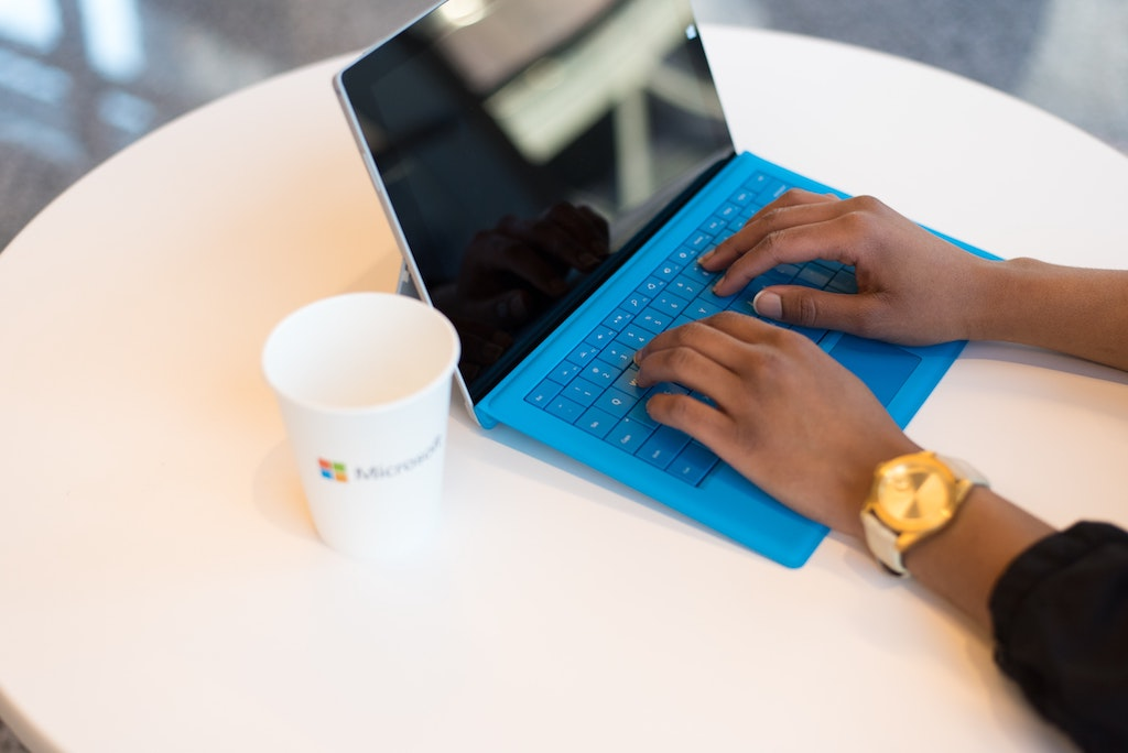 womxn working on her social media on a laptop with a blue keyboard