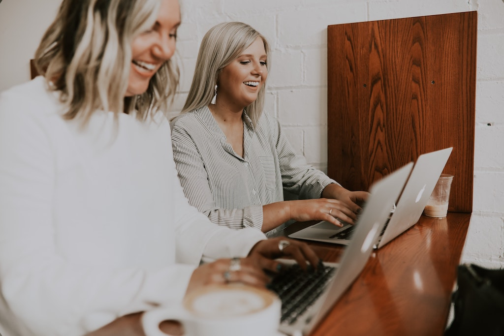 two womxn laughing as they work together from their laptops