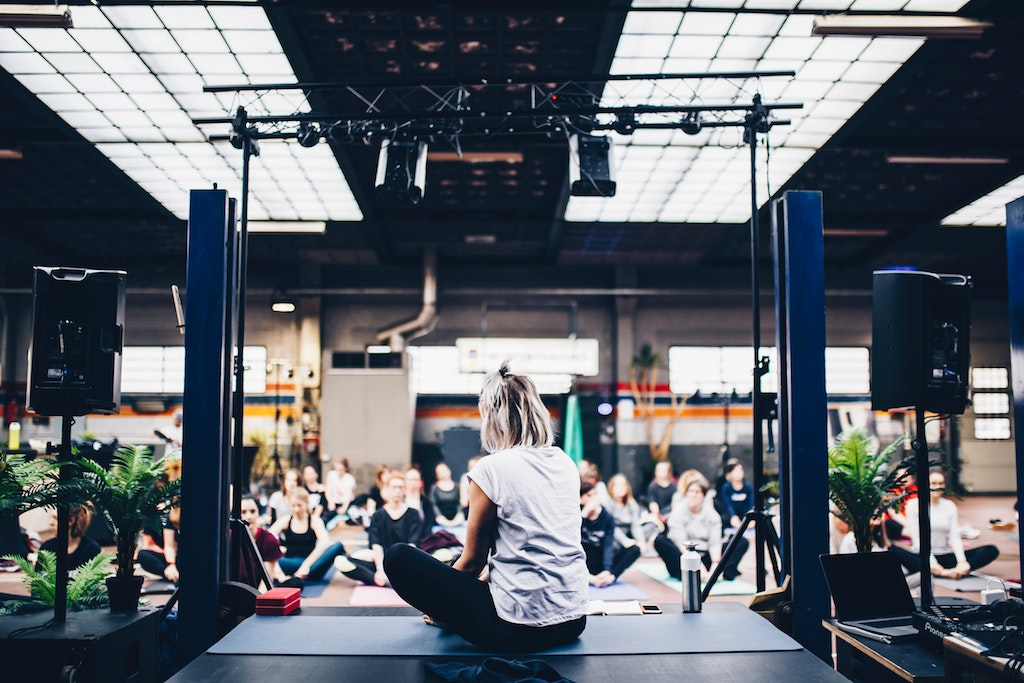 womxn on a stage hosting a yoga class with her back to the camera
