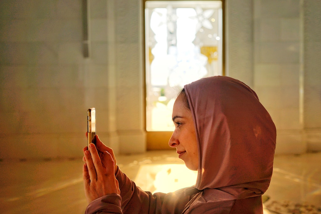 womxn wearing a hedscarf and using her cellphone to take a photo