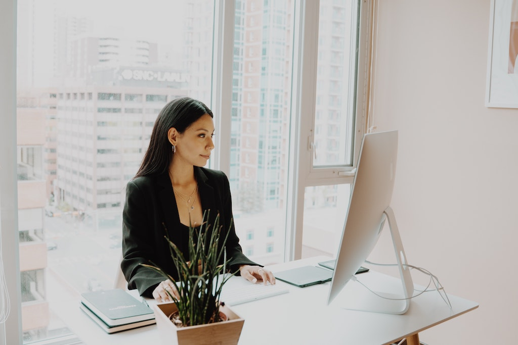 womxn working on her business wearing a black suit and sitting in front of a desktop computer