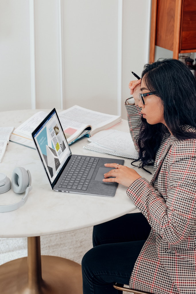 womxn with a laptop and open text books looking at the computer screen