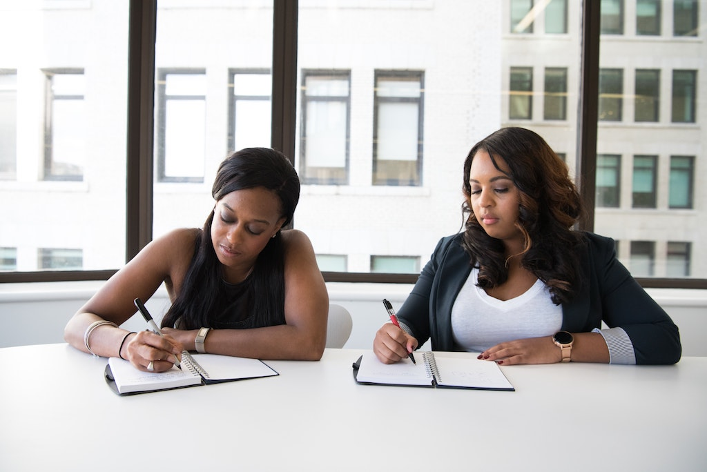 pair of womxn working together to rebrand a small business