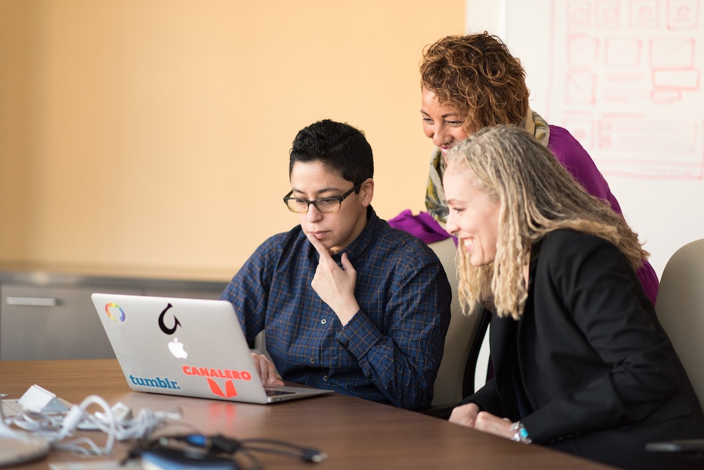 a team of people huddled over a computer and smiling at the screen