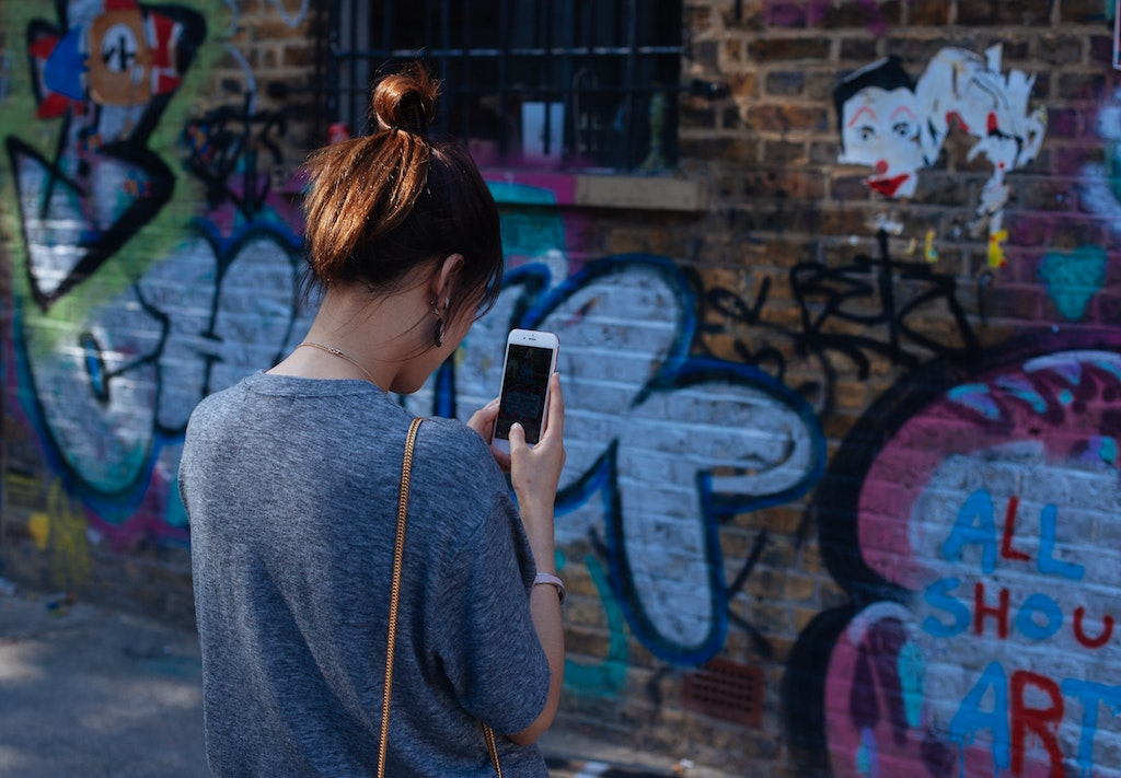 womxn photographing graffiti with her cellphone to upload to social media