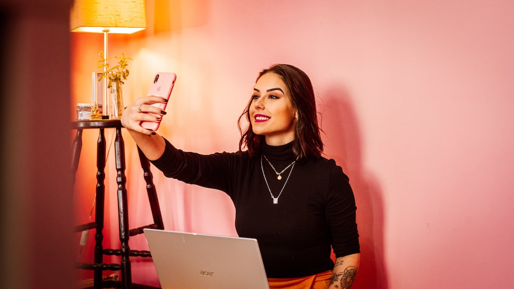 womxn sitting in front of a pink wall and taking a selfie with her mobile phone