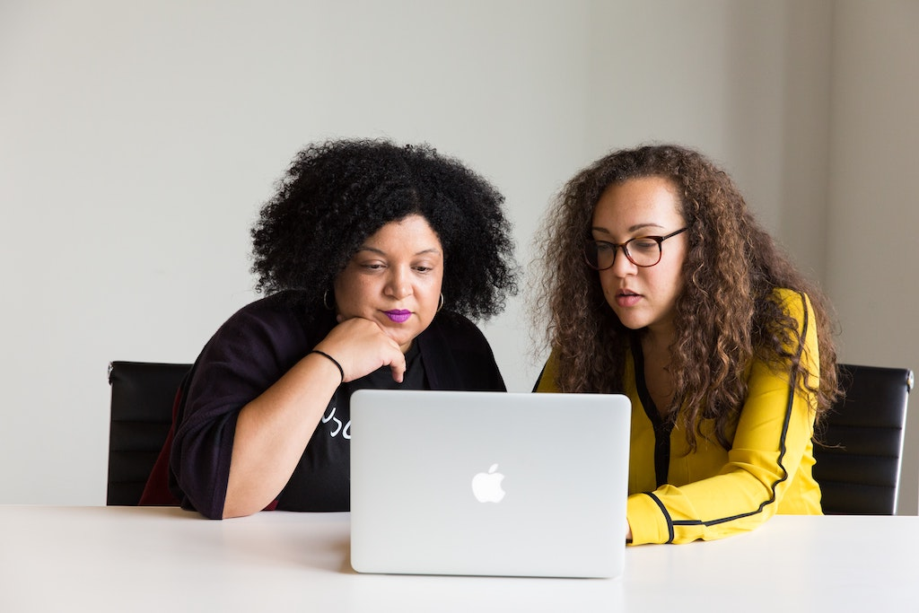 women working at a table with a laptop, deciding which content to repurpose