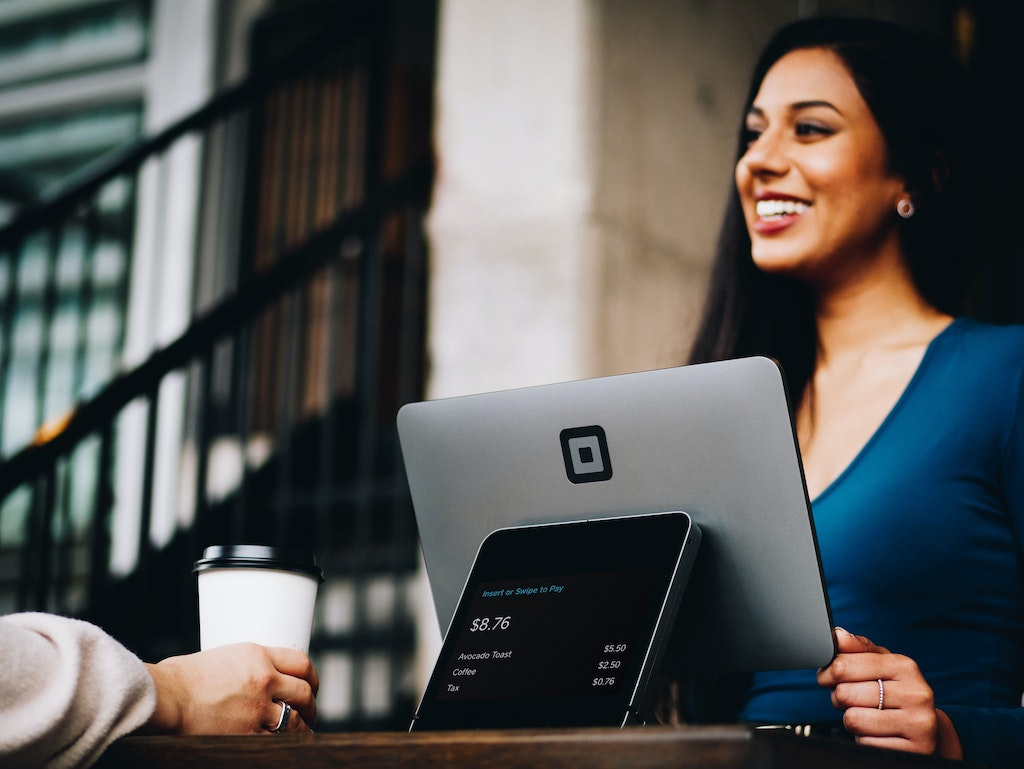 woman smiling at someone else with a laptop in front of her